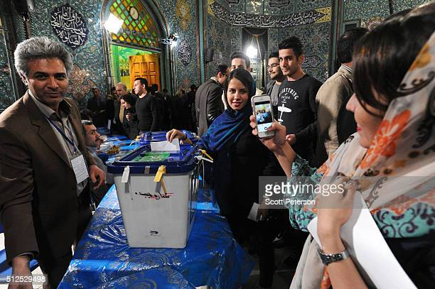 Iranian women take a mobile phone portrait while they vote in key elections for Parliament and the Assembly of Experts in the Hosseiniyeh Ershad...
