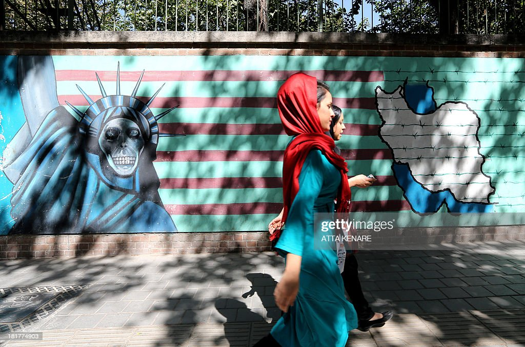 Iranian women walk past a mural showing an interpretation of the Statue of Liberty bearing the face of a skull on the wall of the former US embassy in Tehran on September 25, 2013. Leaders from Iran and the United States have not met since the 1979 Islamic Revolution brought often open hostility to their contacts, particularly over Iran's contested nuclear program.