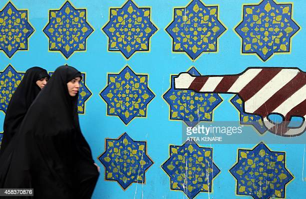 Iranian women walk past a wall of the former US embassy painted with a gun and evoking the US flag on November 4 2014 in Tehran where takes place a...