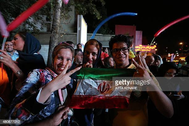 Iranian women wave the national flag and flash the v sign for victory during celebration in northern Tehran on July 14 after Iran's nuclear...