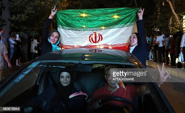 Iranian women wave the national flag during celebration in northern Tehran on July 14 after Iran's nuclear negotiating team struck a deal with world...