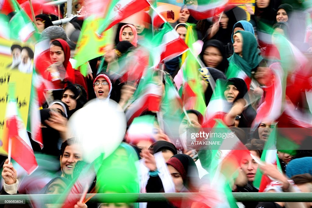 Iranian women wave their national flag during celebrations in Tehran's Azadi Square (Freedom Square) to mark the 37th anniversary of the Islamic revolution on February 11, 2016. Iranians waved 'Death to America' banners and took selfies with a ballistic missile as they marked 37 years since the Islamic revolution, weeks after Iran finalised a nuclear deal with world powers. KENARE