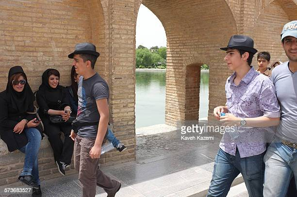 Iranian youth pass by veiled women sat under an arch on Sio Se Pol Bridge on 11th May 2012 in Isfahan Iran
