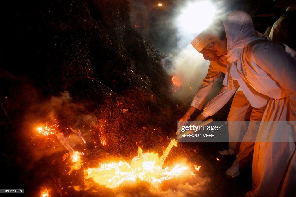 Iranian Zoroastrian priests, Moubad Rashin Jahangir and Moubad Henghami (L) set firewood ablaze in celebration of the annual Zoroastrian Sadeh festival in a western suburb of Tehran on January 29, 2013. Sadeh, is an ancient Persian festival that is celebrated by setting a huge bonfire to honour fire and to defeat the forces of darkness, frost, and cold. Sadeh means 'hundred' and refers to one hundred days and nights past the end of summer.