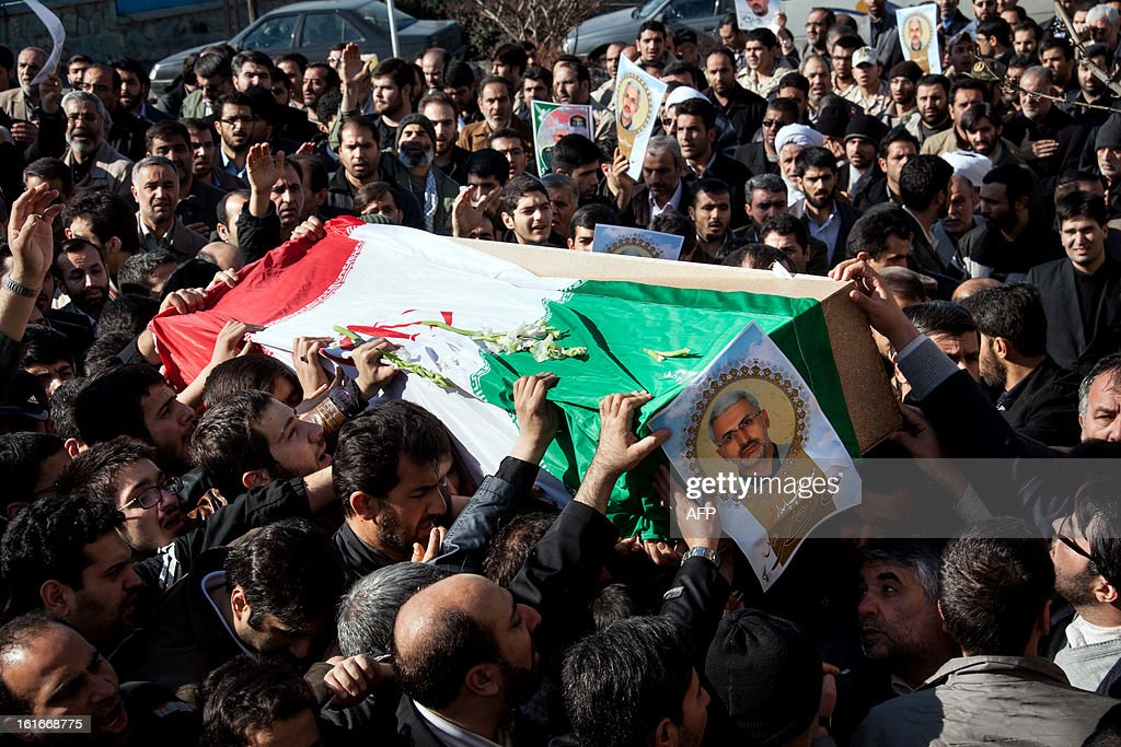 Iranians carry the coffin of Commander Hassan Shateri (portrait), who was shot dead while he was travelling by road in Syria towards the Lebanese capital late on February 13, during his funeral procession in Tehran on February 14, 2013. The Iranian embassy in Beirut said 'armed terrorists' killed Khoshnevis, adding that he had been involved in reconstruction work in Lebanon. The embassy named him as 'Hassan Shateri known as Hessam Khoshnevis'.