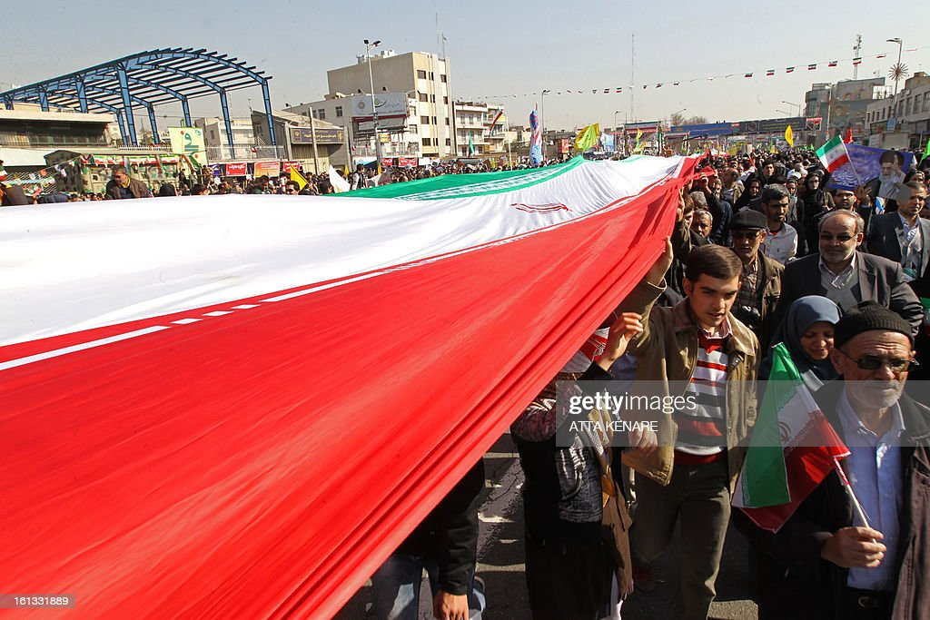 Iranians carry their national flag during a rally in Tehran's Azadi Square (Freedom Square) to mark the 34th anniversary of the Islamic revolution on February 10, 2013. Hundreds of thousands of people marched in Tehran and other cities chanting 'Death to America' and 'Death to Israel' as Iran celebrated the anniversary of the ousting of the US-backed shah.
