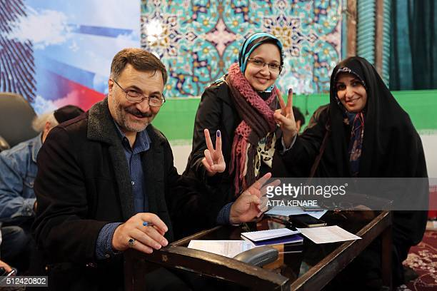 Iranians display their inkstained finger after casting their ballot for both parliamentary elections and the Assembly of Experts at a polling station...