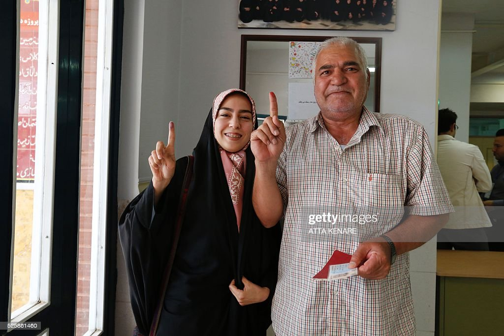 Iranians display their ink-stained fingers after casting their ballot for the second round of parliamentary elections at a polling station in Robat Karim, some 40 kms southwest of the capital Tehran, on April 29, 2016. Iranians started voting in second round elections for almost a quarter of parliament's seats, the latest political showdown between reformists and conservatives seeking to influence the country's future. Polling stations opened at 8:00 am (0330 GMT) for the ballot which is taking place in 21 provinces, but not Tehran, because no candidate in 68 constituencies managed to win 25 percent of votes cast in initial voting on February 26. Reformists who backed moderate President Hassan Rouhani made big gains in the first round following Iran's implementation of a nuclear deal with world powers, which lifted sanctions blamed for long hobbling the economy. Conservative MPs, including vehement opponents of the West who openly criticised the landmark agreement that reined in Iran's atomic programme, lost dozens of seats and were wiped out in Tehran where reformists won all 30 places in parliament. / AFP / ATTA