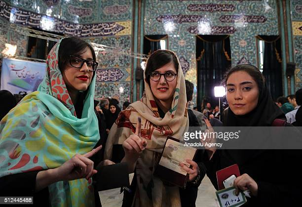 Iranians display their inkstained fingers after casting their ballots for both parliamentary elections and the Assembly of Experts at a polling...