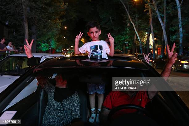 Iranians flash the v sign for victory as they drive during celebration in northern Tehran on July 14 after Iran's nuclear negotiating team struck a...