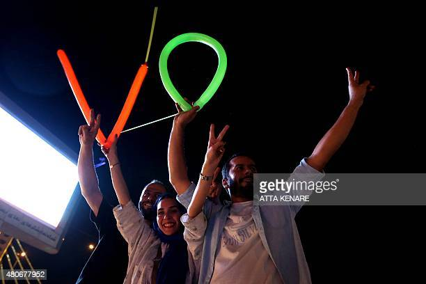 Iranians flash the v sign for victory during celebration in northern Tehran on July 14 after Iran's nuclear negotiating team struck a deal with world...