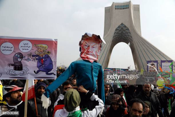 Iranians hold a dummy representing US President Donald Trump during a rally marking the anniversary of the 1979 Islamic revolution on February 10 in...