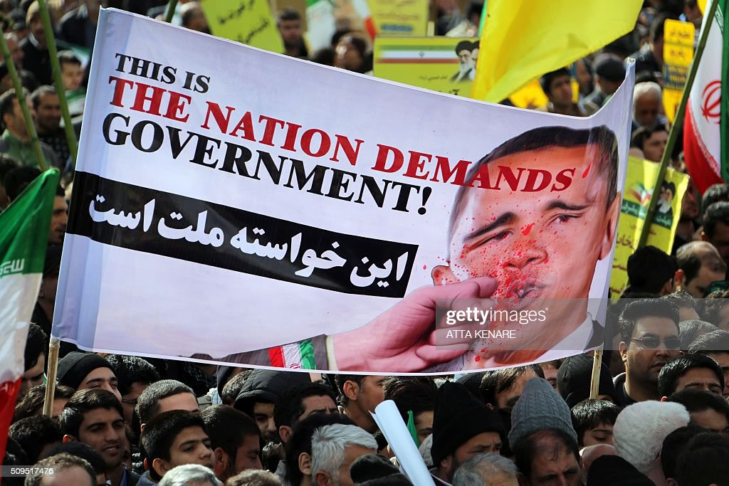 Iranians hold an anti-US slogan during celebrations in Tehran's Azadi Square (Freedom Square) to mark the 37th anniversary of the Islamic revolution on February 11, 2016. Iranians waved 'Death to America' banners and took selfies with a ballistic missile as they marked 37 years since the Islamic revolution, weeks after Iran finalised a nuclear deal with world powers. KENARE