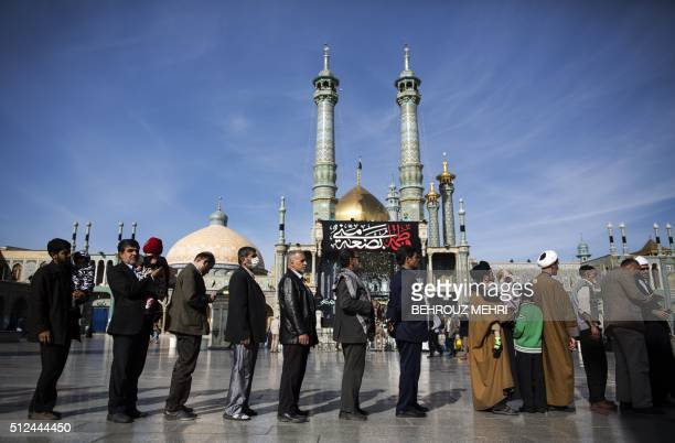 Iranians hold their identification cards as they line up outside a polling station at Massoumeh shrine during the parliamentary and Assembly of...