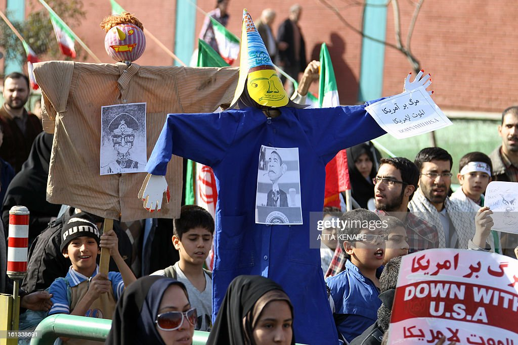 Iranians hold up two effigies, one with the image of US President Barack Obama (front) pinned to it and the other with an image the late and deposed Shah of Iran, during a rally in Tehran's Azadi Square (Freedom Square) to mark the 34th anniversary of the Islamic revolution on February 10, 2013. Hundreds of thousands of people marched in Tehran and other cities chanting 'Death to America' and 'Death to Israel' as Iran celebrated the anniversary of the ousting of the US-backed shah.