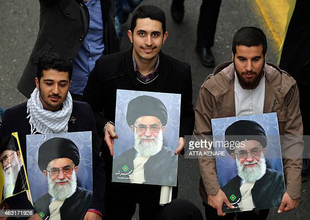 Iranians hols posters of Iran's supreme leader Ayatollah Ali Khamenei during a rally in Tehran's Azadi Square to mark the 36th anniversary of the...