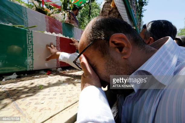 Iranians mourn during the funeral of the victims of the attacks on Tehran's parliament complex and the shrine of revolutionary leader Ayatollah...