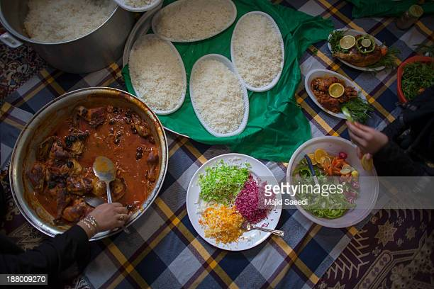 Iranians prepare food for needy people during the Ashura mourning feast November 14 2013 in the village of Bagh Malek 480 Km south of Tehran Iran The...