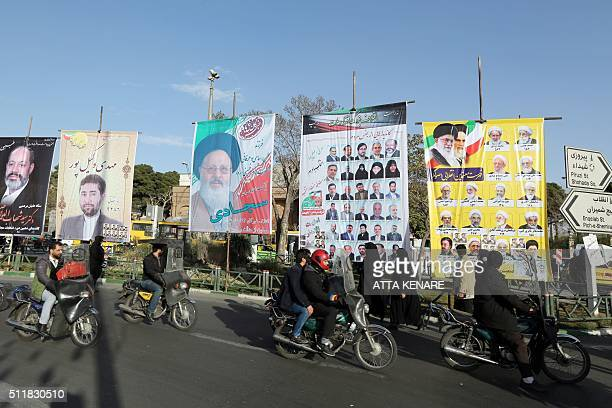 Iranians ride past campaign posters for upcoming parliamentary elections in downtown Tehran on February 23 2016 Voters will take part in two ballots...