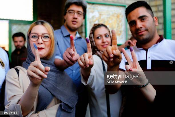 Iranians show their inkstained fingers after casting their ballots for the presidential elections at a polling station in southern Tehran on May 19...