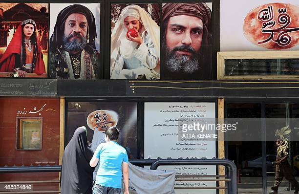 Iranians stand in front of a movie theatre featuring the awaited multimilliondollar film 'Muhammad' in Tehran on August 27 on the first day of...