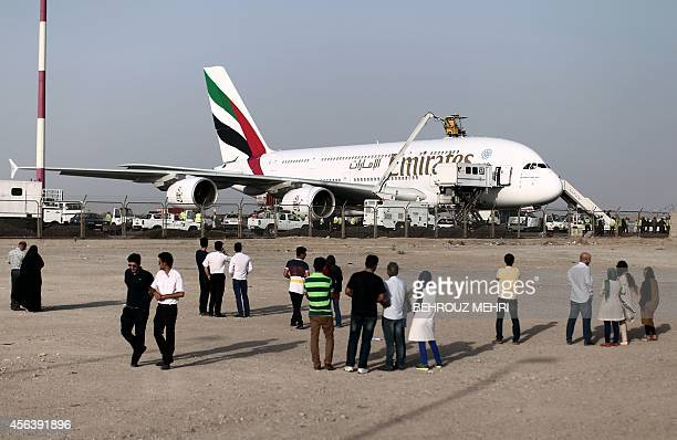 Iranians stand looking at an Airbus A380800 airctaft of Emirates Airline after it landed at Tehran's IKA international airport on September 30 2014...