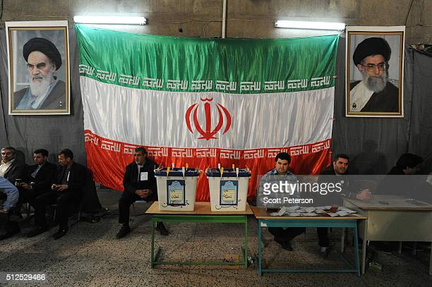 Iranians vote in key elections for Parliament and the Assembly of Experts in front of a large Iranian flag at the Rasoul mosque in the Nazi Abad...
