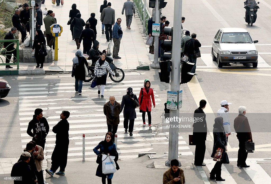 Iranians walk in the streets of the capital Tehran on November 24 2013 a day after a deal was reached on the country's nuclear programme President...