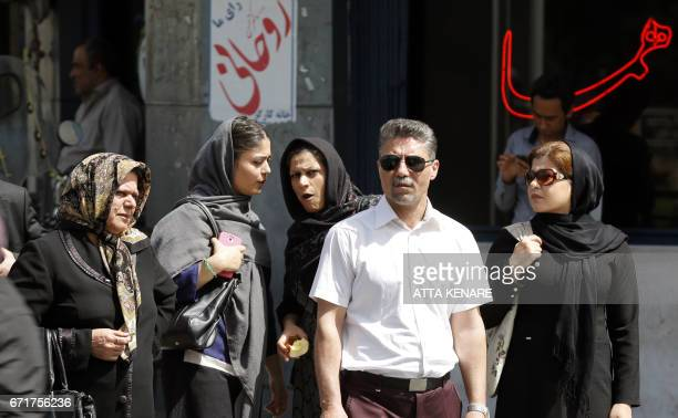 Iranians walk past election posters of President Hassan Rouhani who is running for the presidential elections in Tehran on April 23 2017 / AFP PHOTO...