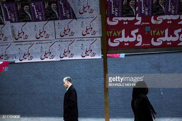 Iranians walk past electoral posters for upcoming parliamentary elections displayed at a bus station in downtown Tehran on February 22 2016 / AFP /...