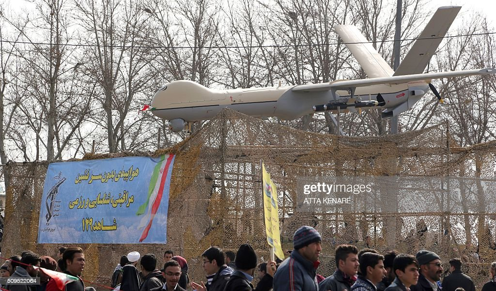 Iranians walk past Iran's Shahed 129 drone during celebrations in Tehran to mark the 37th anniversary of the Islamic revolution on February 11, 2016. Iranians waved 'Death to America' banners and took selfies with a ballistic missile as they marked 37 years since the Islamic revolution, weeks after Iran finalised a nuclear deal with world powers. KENARE