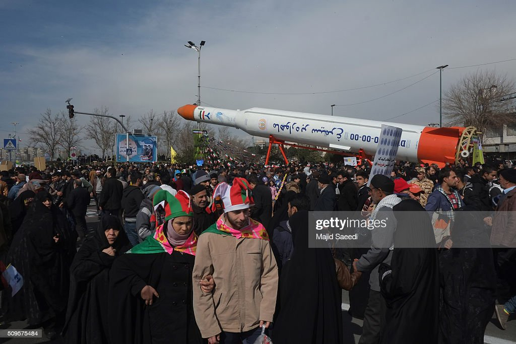 Iranians walk past the Simorgh (Phoenix) satellite rocket during celebrations to mark the 37th anniversary of the Islamic revolution in Azadi Square (Freedom Square) on February 11, 2016 in Tehran, Iran. Rallies and celebrations are being held across the country. President Hassan Rouhani has urged the public to turn out for the upcoming parliamentary and Constitutional Council elections.
