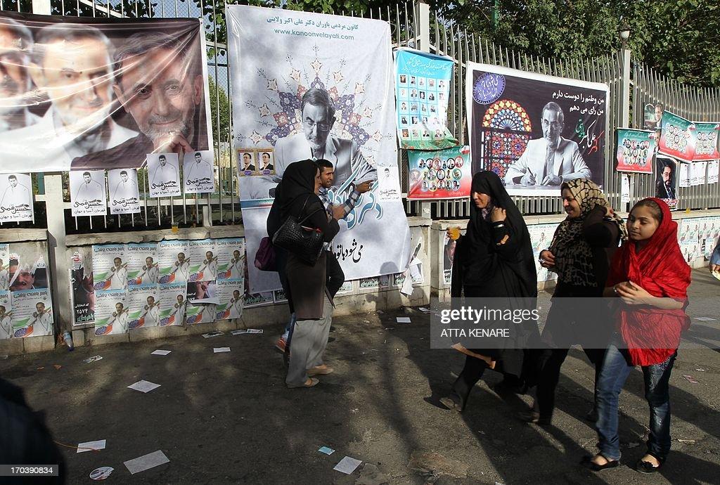 Iranians walks past portraits of Iranian advisor to the supreme leader Ayatollah Ali Khamenei and hopeful conservative presidential candidate, Ali Akbar Velayati during his campaign rally in Tehran, on June 12, 2013.