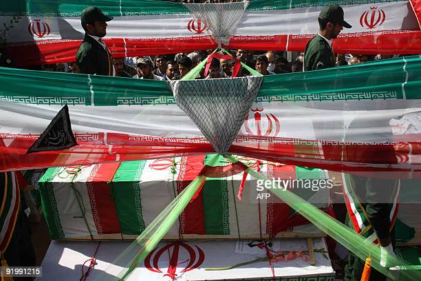 Iranians watch the funeral procession of Iran's elite Revolutionary Guards and local tribesmen in Zahedan near the Pakistani border on October 19...