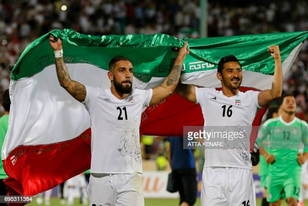 Iran's Ashkan Dejagah Reza Ghoochannejad celebrates among players after winning the 2018 World Cup qualifying football match between Iran and...