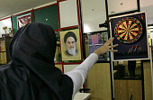 Iran's dart national team member Sahar Zohouri throws a dart next to a portrait of Iran's late founder of Islamic republic Ayatollah Khomeini during...