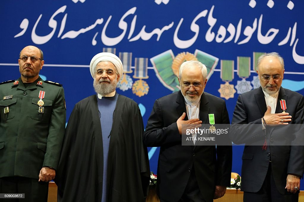 Iran's Defence Minister Hossein Dehghan (L), Foreign Minister Mohammad Javad Zarif (2nd from R) and Ali Akbar Salehi (R), the head of Iran's Atomic Energy Organisation, pose for pictures after receiving the Medal of Honour from President Hassan Rouhani (2nd from L) for their role in the implementation of a nuclear deal with world powers, on February 8, 2016, in Tehran. / AFP / ATTA KENARE