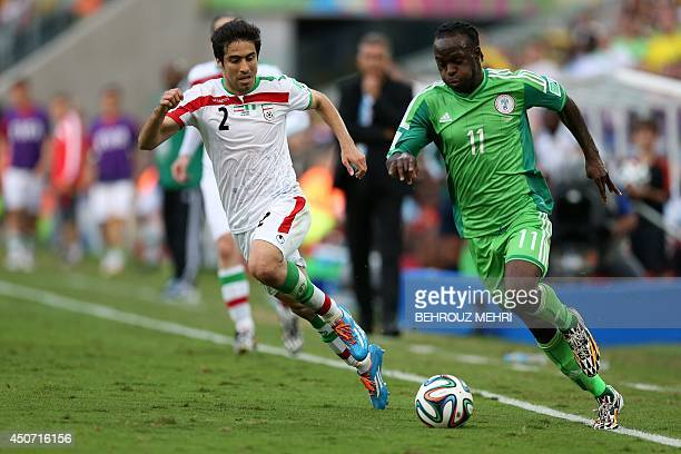 Iran's defender Khosro Heidari fights for the ball with Nigeria's forward Victor Moses during a Group F football match between Iran and Nigeria at...