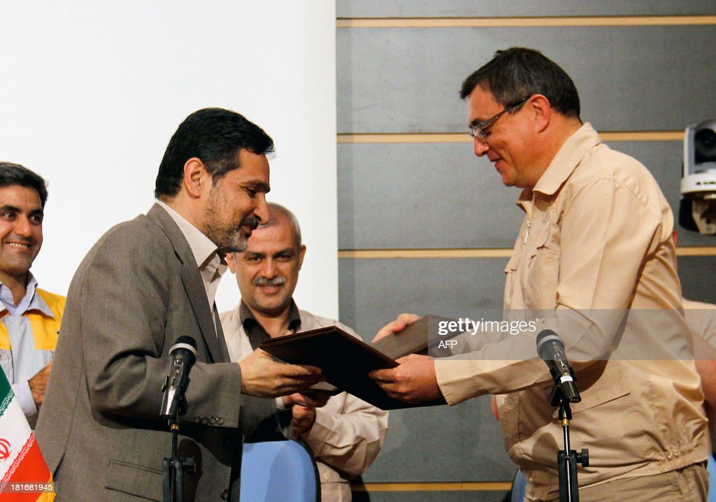 Iran's Deputy Head of Atomic Energy Organization Mohammad Ahmadian (L), and Valery Limarenko, the General Designer of the Bushehr nuclear power plant, exchange signed documents at the Russian-Built nuclear power plant in the southern city of Bushehr, on September 23, 2013. Iran finally took control of its civilian nuclear reactor at Bushehr, a project begun 37 years ago by West Germany, wracked by setbacks, and finished by Russia.