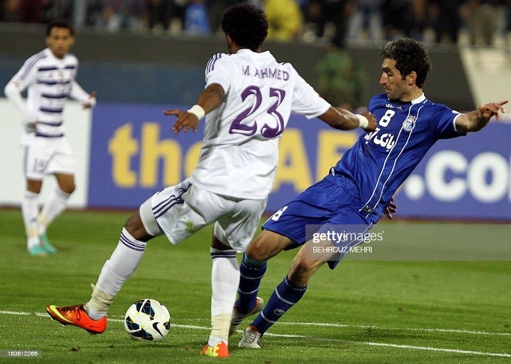 Iran's Esteghlal Captain Mojtaba Jabari (R) challenges UAE's Al-Ain players Muhammed Ahmed Gharib (C) during their AFC Champions League group D football match at Azadi stadium in Tehran on March 13, 2013. Esteghlal won 2-0.