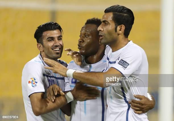 Iran's Esteghlal Khouzestan forward Aloys Nong celebrates with his teammates Hassan Beit Saeid and Mehdi Momeni Larimi after scoring a goal during...