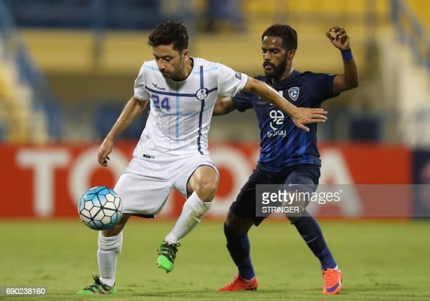 Iran's Esteghlal Khouzestan midfielder Aliasghar ashouri is tacked by Saudi Arabia's AlHilal midfielder Nawaf AlAbid during the AFC Champions League...