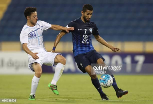 Iran's Esteghlal Khouzestan midfielder Aliasghar Ashouri tackes Saudi Arabia's AlHilal midfielder Salman AlFaraj during the AFC Champions League...