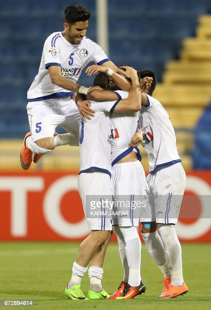 Iran's Esteghlal Khuzestan defender Aghil Kaabi jumps on his teammates as they celebrate after scoring a goal during the AFC Champions League...