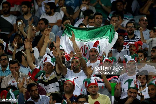 Iran's fans cheer during the 2018 World Cup qualifying football match between Iran and Uzbekistan at the Azadi Stadium in Tehran on June 12 2017 /...