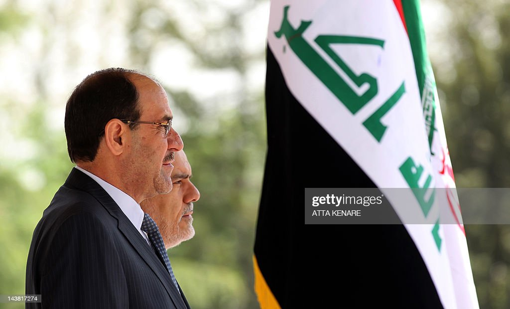 Iran's First Vice President Mohammad Reza Rahimi (R) and Iraqi Prime Minister Nouri al-Maliki (L) listen to their national anthems during a welcoming ceremony in Tehran on April 22, 2012 upon the latter's arrival for two days of meetings with Iranian leaders and senior officials on various bilateral issues. The visit notably comes ahead of an important May 23 meeting to be hosted in Baghdad between Iran and the P5+1 group of world powers on Tehran's disputed nuclear programme. AFP PHOTO/ATTA KENARE