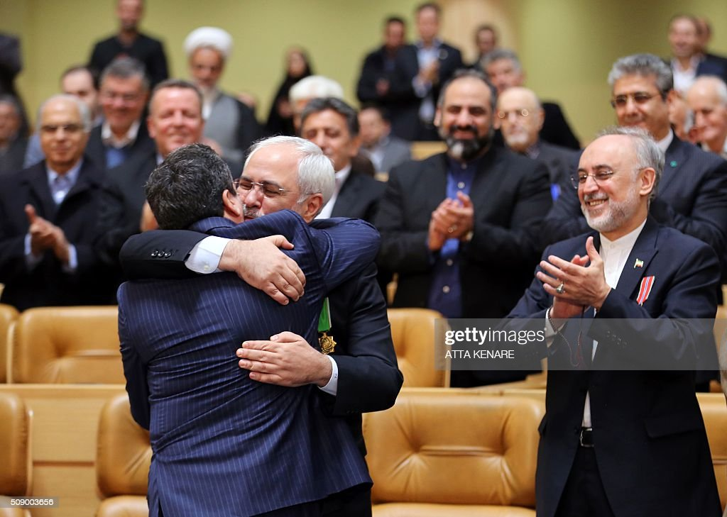 Iran's Foreign Minister Mohammad Javad Zarif (C-R) hugs Iran's deputy foreign minister Abbas Araghchi as Ali Akbar Salehi, the head of Iran's Atomic Energy Organisation, applauds after receiving the Medal of Honour for their role in the implementation of a nuclear deal with world powers, on February 8, 2016, in Tehran. / AFP / ATTA KENARE