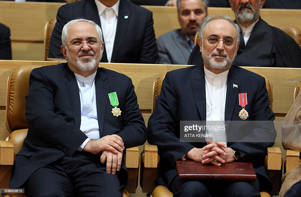 Iran's Foreign Minister Mohammad Javad Zarif (L) sits next to Ali Akbar Salehi, the head of Iran's Atomic Energy Organisation, after they received the Medal of Honour for their role in the implementation of a nuclear deal with world powers, on February 8, 2016, in Tehran. / AFP / ATTA KENARE