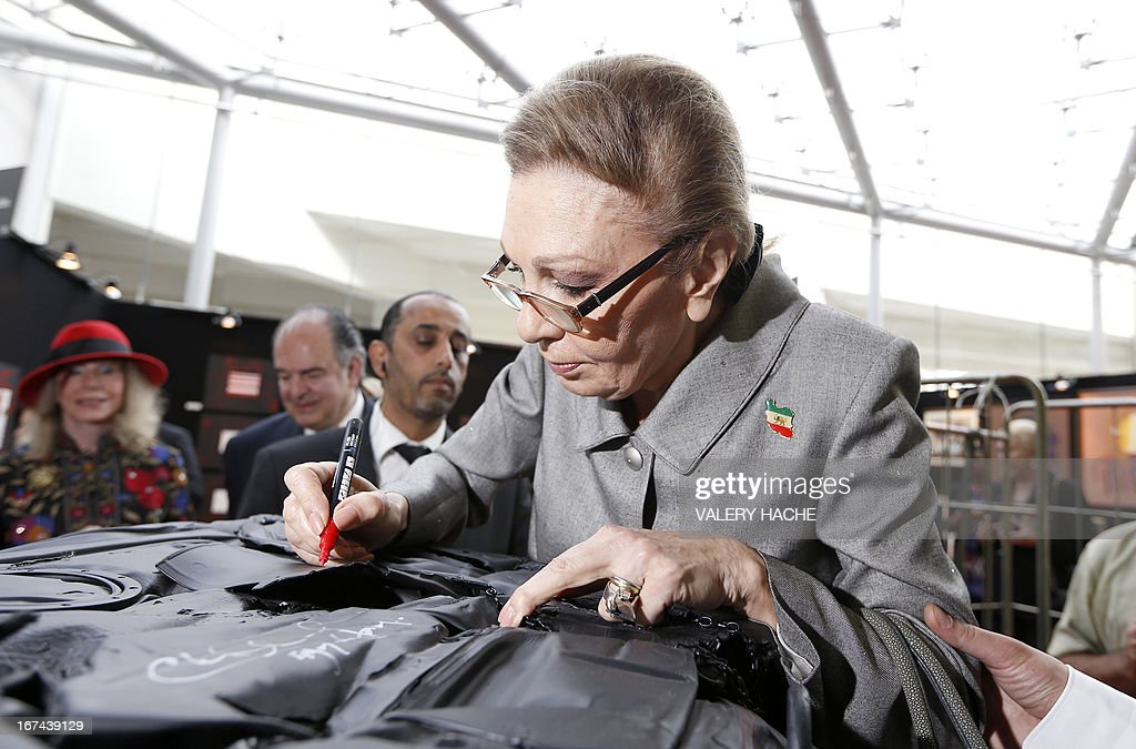Iran's former Queen Farah Pahlavi signs an autograph as she visits the 4th edition of the 'Art Monaco' contemporary art fair on April 25, 2013 in Monaco. The event takes place from April 25 to 28.