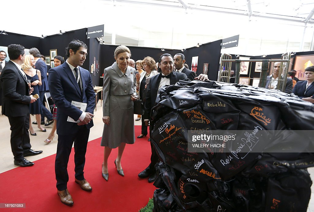Iran's former Queen Farah Pahlavi (C) stands next to an artwork as she visits the 4th edition of the 'Art Monaco' contemporary art fair on April 25, 2013 in Monaco. The event takes place from April 25 to 28.